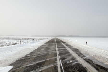 Snowing road in the middle of snow fields Stock Photo - 17240512
