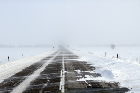 Snowing road in the middle of snow fields Stock Photo - 17240514