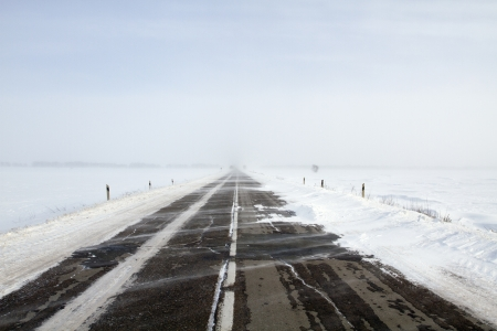 Snowing road in the middle of snow fields Stock Photo - 17240513