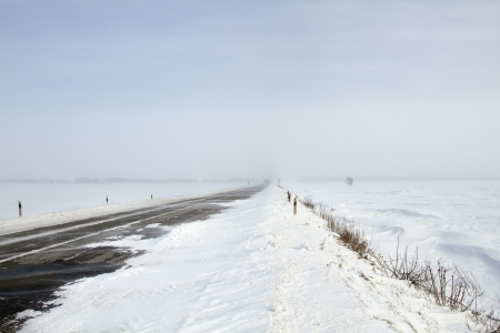 Snowing road in the middle of snow fields Stock Photo - 17240510
