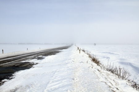 Snowing road in the middle of snow fields Stock Photo - 17239856