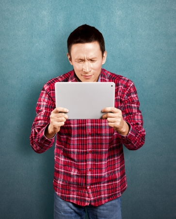 Asian man with touch pad in his hands embarrassed with news photo
