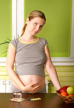 Pregnant woman on kitchen with water and pills photo