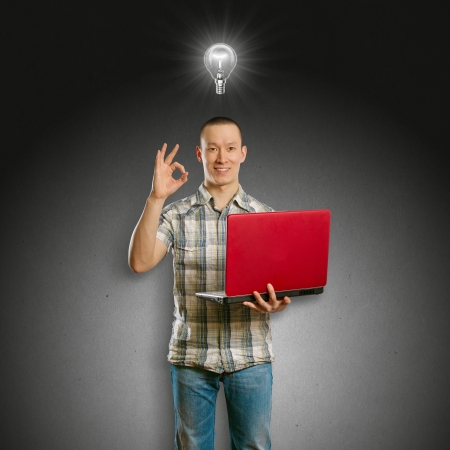 Idea concept. Asian male with laptop in his hands shows OK, with lamp above his head photo