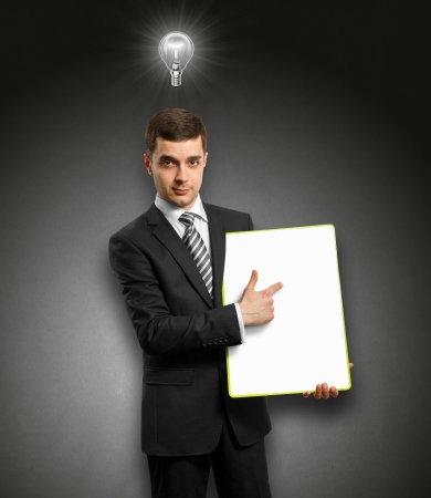 Idea concept. Businessman holding empty write board in his hands, with lamp above his head photo