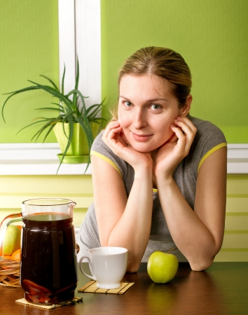 Pregnant woman on kitchen, with cup, compote and apple photo