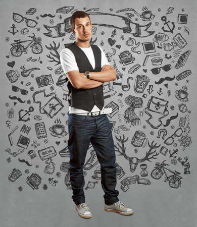 Man hipster in vest, looking on camera, with folded hands photo