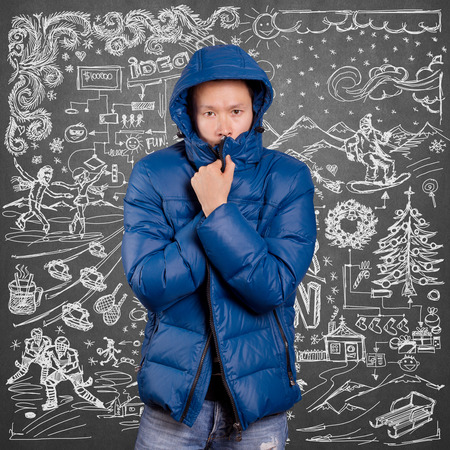 Asian man in blue down-padded coat, with winter fun sketch background photo