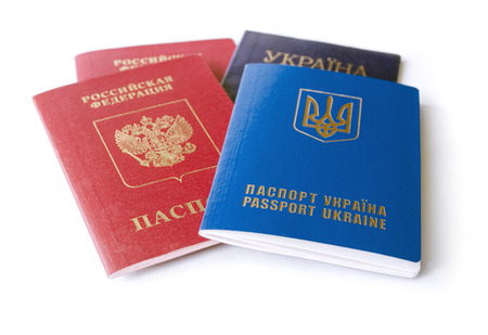 martial law: Ukrainian and Russian ID passports isolated on white background, means conflict between two countries