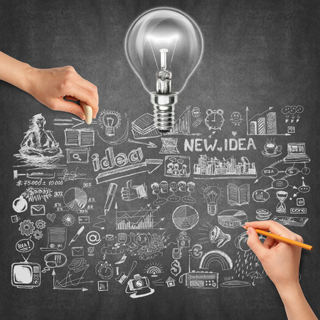 Idea background with lamp, sketch and human hand with pencil photo