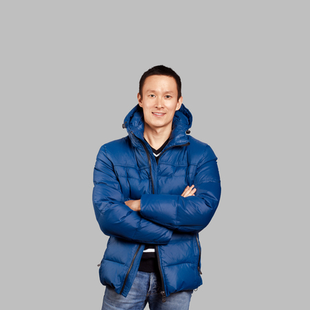 Asian man in blue down-padded coat, isolated on trendy gradient background