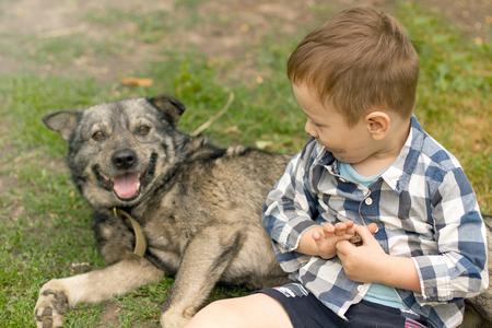 Child lovingly embraces his pet dog. Boy hugging his dog