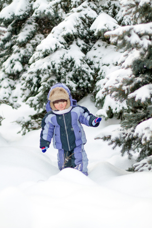 Boy enjoying the first snow in the november. Waiting for the Cristmas