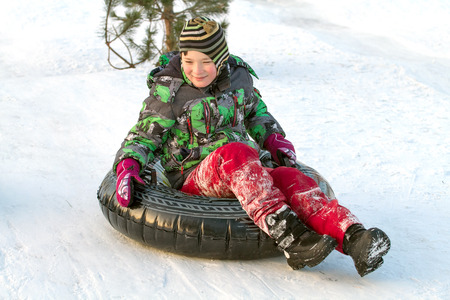 Happy boy with snow tube. Winter fun. Sliding down the hill on a snow tube Imagens