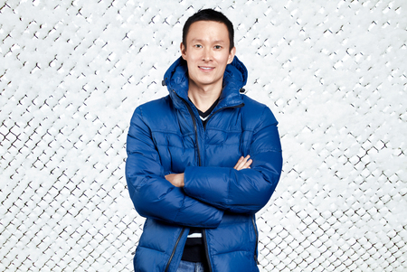 Happy Asian man in blue down padded coat, against snowy winter background. Man outdoors in warm winter clothes. Snow and cold