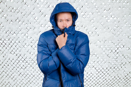 Sad Asian man in blue down padded coat, against snowy winter background. Man outdoors in warm winter clothes. Snow and cold
