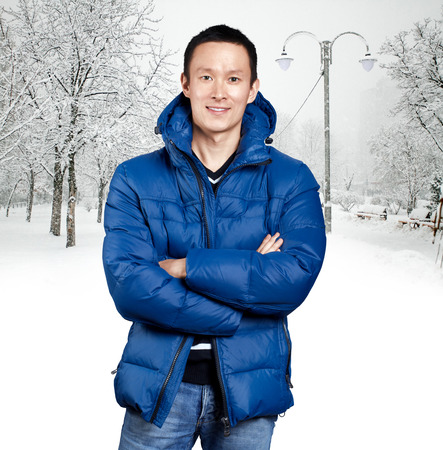 Happy Asian man in blue down padded coat, against snowy winter background. Man outdoors in warm winter clothes. Snow and cold Foto de archivo