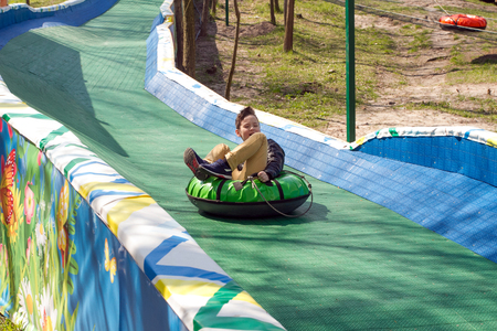 Happy boy with tube. Spring, autumn and summer fun. Sliding down the hill on a tube