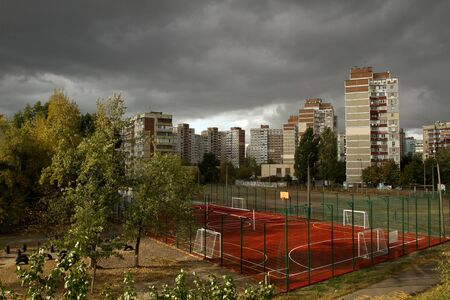 Urban landscape with dark storm sky. Sun and dark sky clouds. Global warming concept
