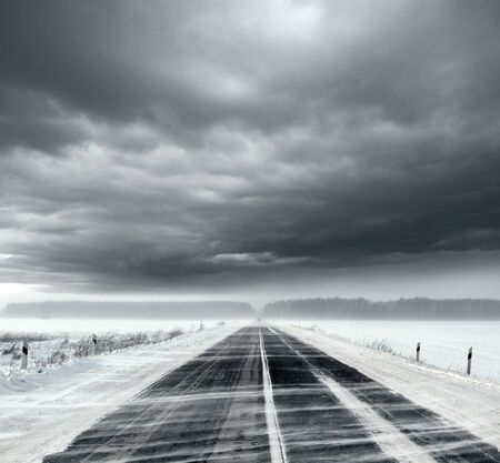 Beautiful stormy sky with clouds and snow road. Snow road in the middle of snow fields Stock Photo