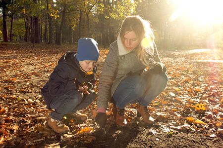 Son and Mother in the Park. Boy and Mother are writing something on the ground, in the autumn park Banque d'images