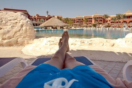 Happy man on vacation. Man in the deck chair near the swimming pool with blue water