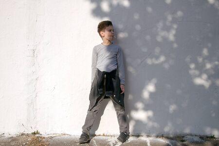 Cute serious boy against white wall. Boy with blue lollipop