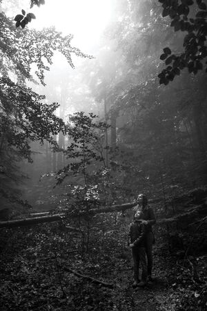 Mother and son in the mystic green foggy forest. The are looking up waiting for the miracle