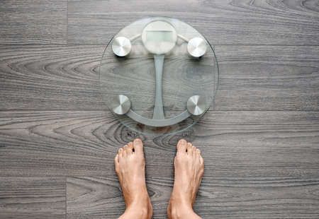 Image of human feet standing on electronic scales, on gray background, top view, diet concept