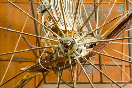 rusting: Metal cart wheel in a rusting barn.  Old machinery.