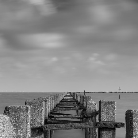 groynes: A shot of groynes jutting out into the sea.  Taken with a long exposure to make the clouds and water misty. Stock Photo