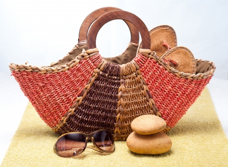 Straw beach bag with slipslops and sunglasses on beach towel photo