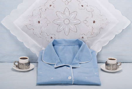 roomservice: Blue pajama and espresso cups and lace pillow on blue and white striped bed