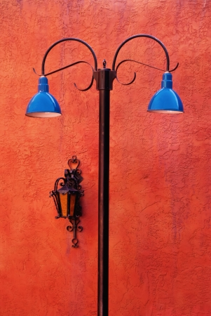 southwestern: Two blue lights and old lamp on terracotta wall
