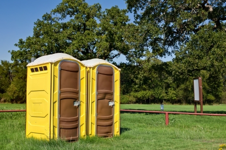 public bathroom: Two yellow portable toilets at a park
