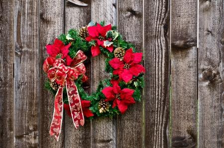 flor de pascua: Navidad corona de flores en la cerca de madera r�stica Foto de archivo