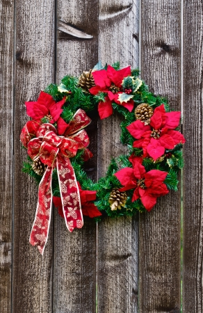 Christmas flower wreath on rustic wooden fence Stock Photo