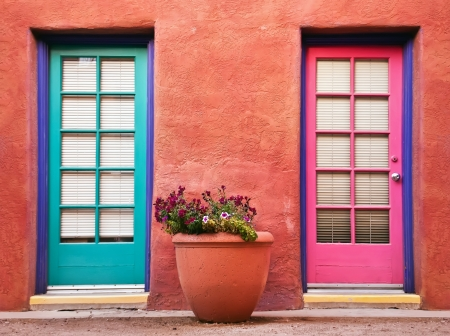 southwestern: Colorful doors and flower pot against terracotta wall