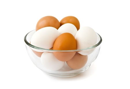 Fresh eggs in the glass bowl over white