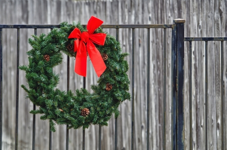 Christmas spruce fir wreath hanging on iron fence against gray background photo