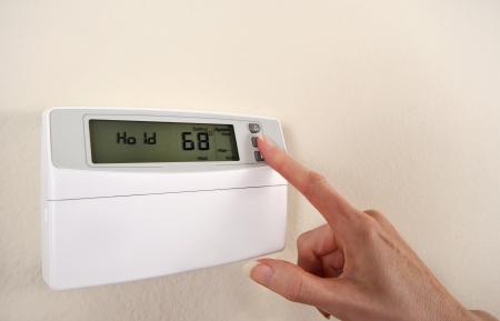 Aanpassen en het instellen van thermostaat om energie te besparen Stockfoto