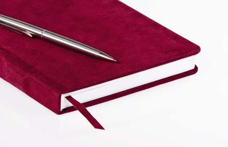 Red journal and a pen over white background Stock fotó