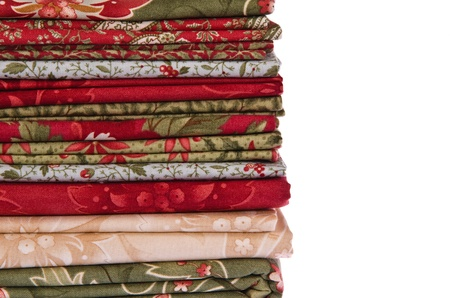 Quilting fabrics in different colors and patterns over white with copy space Imagens