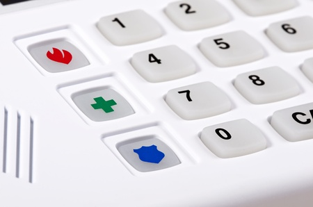 Closeup of home security alarm keypad with fire, police, and medical emergency buttons, shallow depth of field