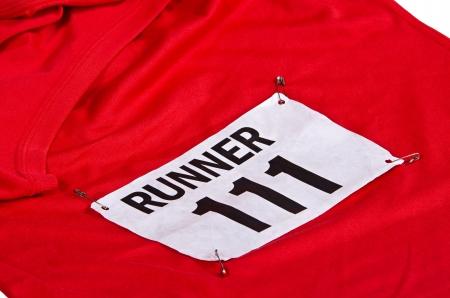babero: N�mero de carrera en babero unido a la parte delantera de la camisa rojo ejecutan Foto de archivo