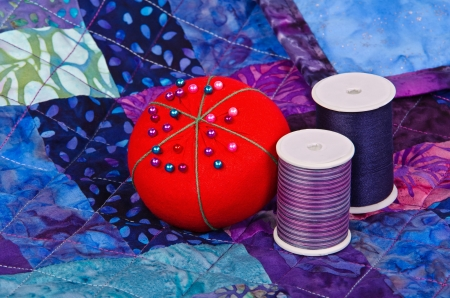 Quilt pattern with quilting thread and pincushion photo