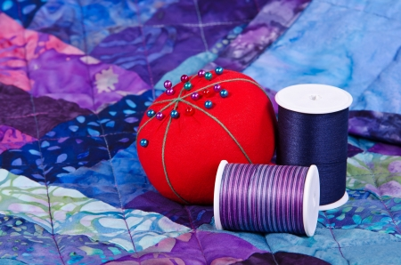patchwork pattern: Quilting thread and pincushion on the top of the quilt Stock Photo