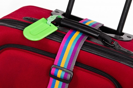 luggage tag: Closeup of bright green luggage tag and colorful belt on red suitcase