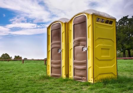 Twee gele draagbare toiletten in een park