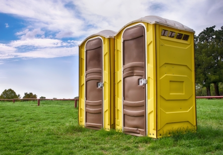 portables: Two yellow portable toilets at a park